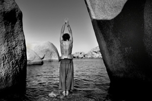 Yoga posture on a rock in a mountain lake